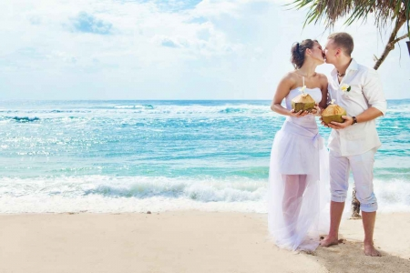 A bride and groom kissing on the beach holding several coconut drinks.