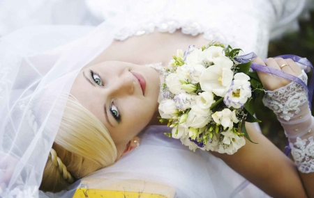 A bride laying down on a bench with a flower bouquet and very beautiful hair.