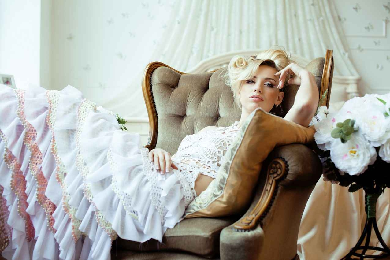 A bride with absolutely beautiful hair relaxed and sitting in a resort chair waiting for her wedding to begin.