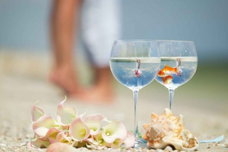 Two fish swimming together in two champagne glasses with a bride and groom visibly kissing in the reflection.
