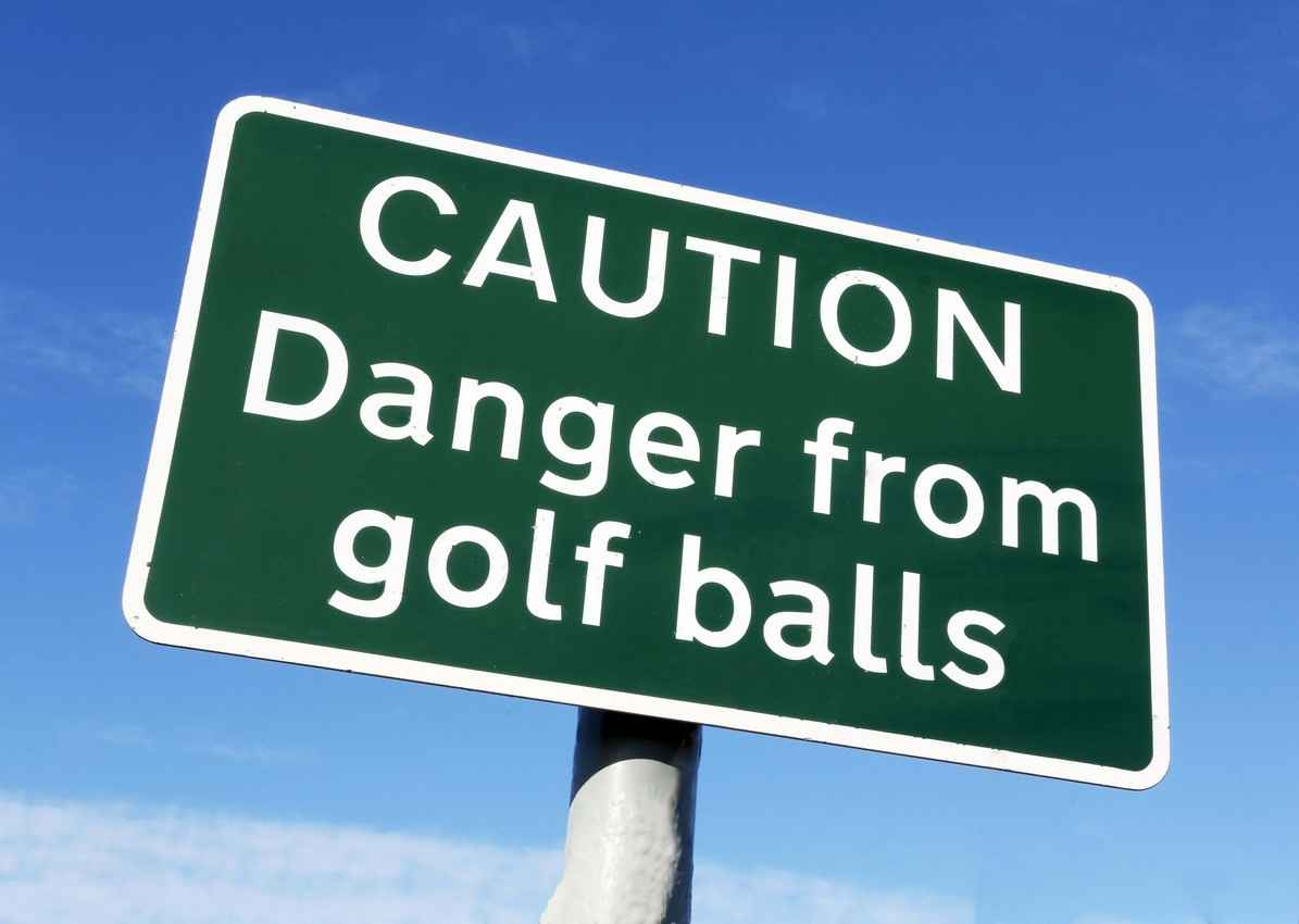 A sign that says, caution danger from golf balls.