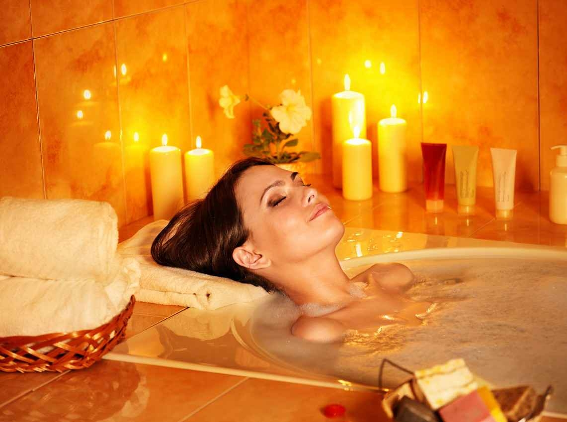 A pretty woman taking a candlelit bath at an exclusive resort.