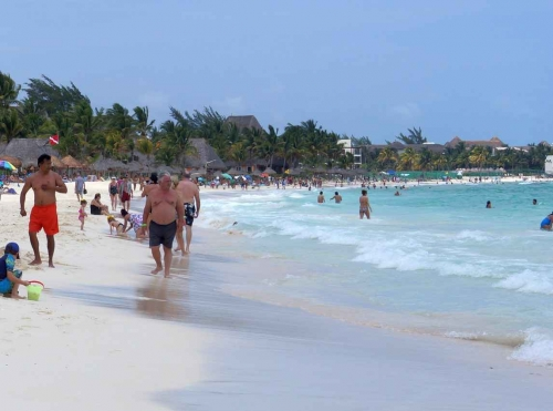 The Playa Del Carmen beach busy with people walking and swimming.