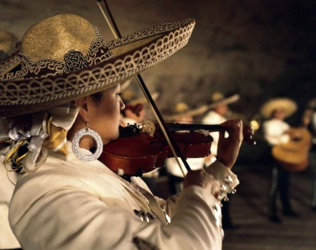 A Mexican woman wearing a sombrero and playing a violin.