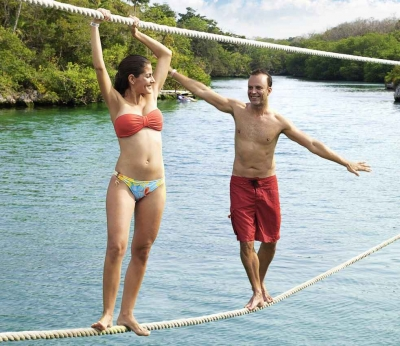 A man and a woman walking along a double rope line above the water.