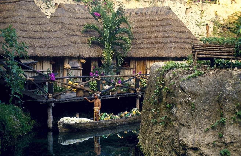A Mayan man sitting in the canoe near several villas.