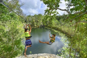 Two kids playing on a zip line near a cenote.