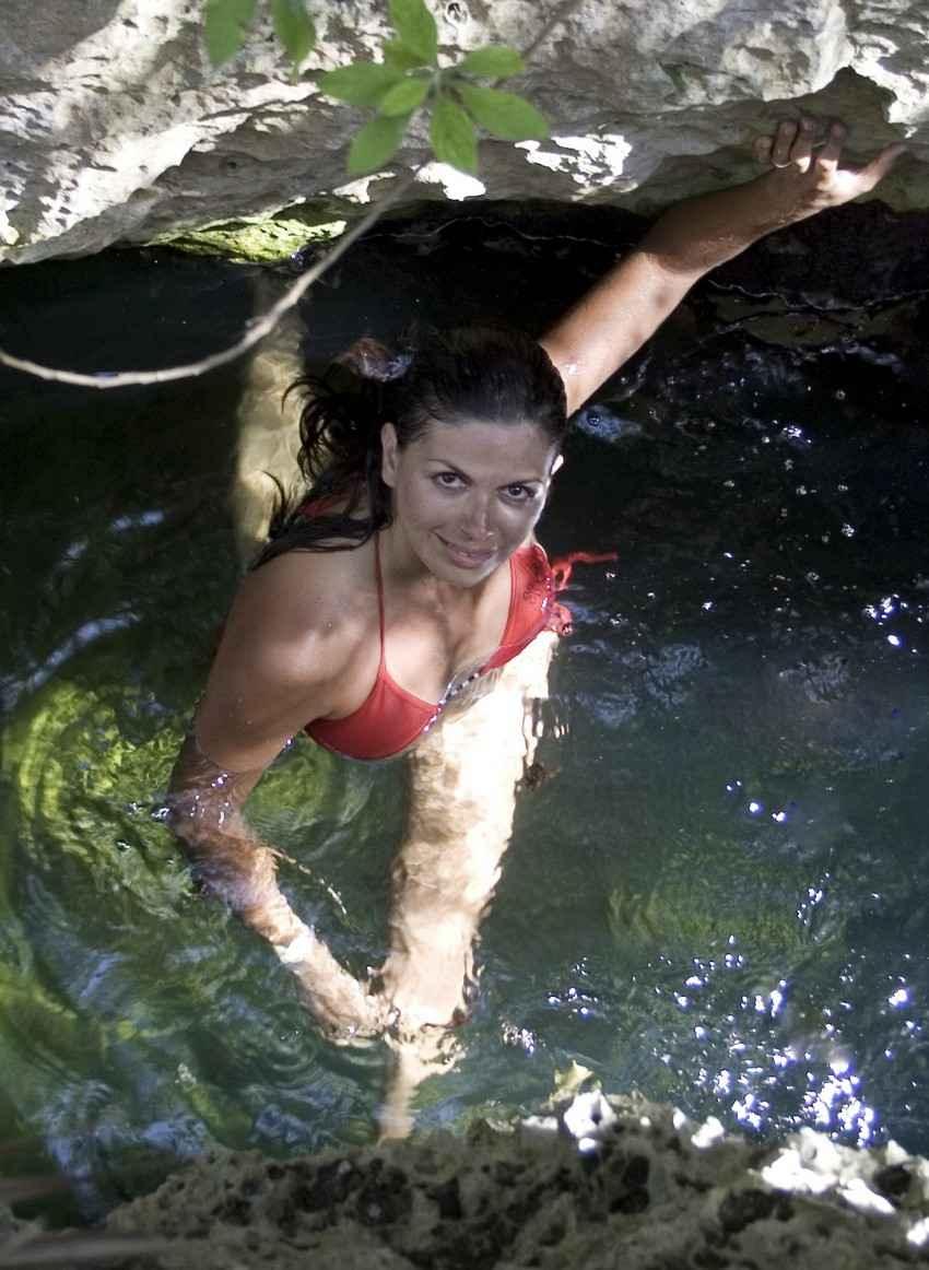 Looking down from above on a beautiful woman who is wearing a red bikini and swimming in a cenote.