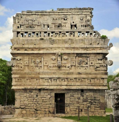 A large Mayan building in the center of ancient ruins.