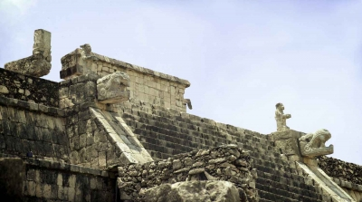 Statues of both a lizard and a snake on the side of a Mayan pyramid.