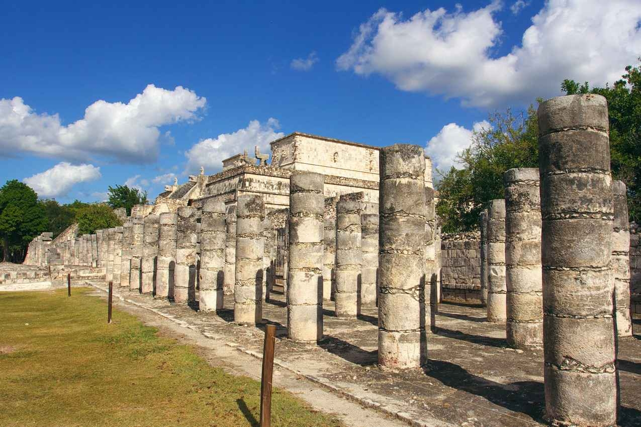 Several rows of columns in front of a building at Chichen Itza.