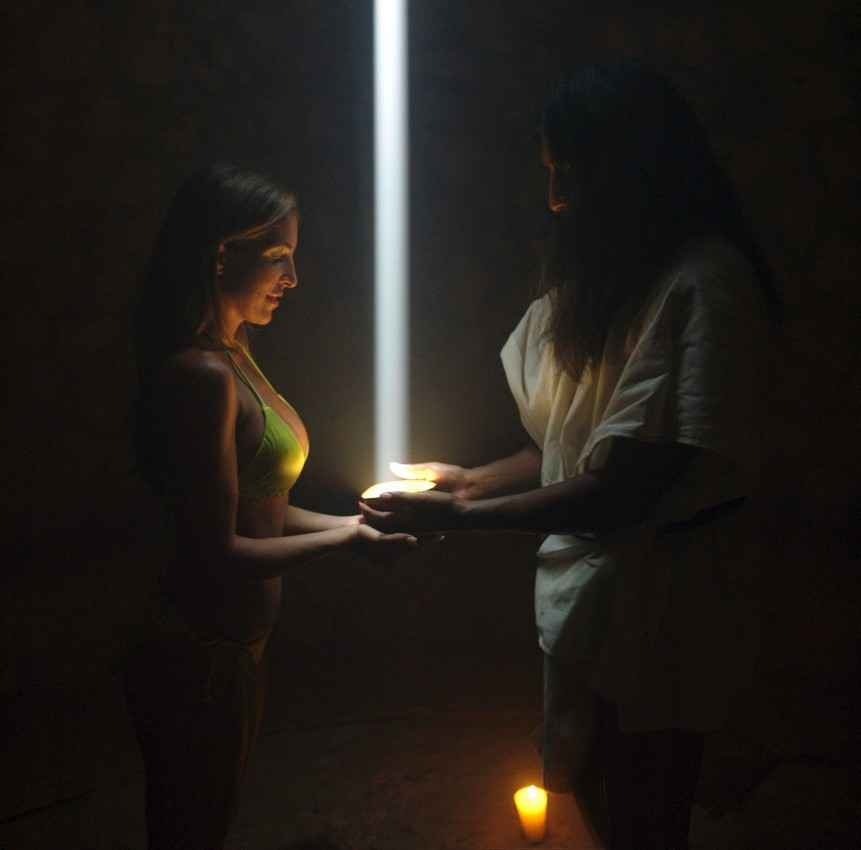 A Mayan rejuvenation ceremony being performed on a sexy female tourist in a bikini.